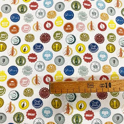 Tissu coton imprimé capsules bières mètre